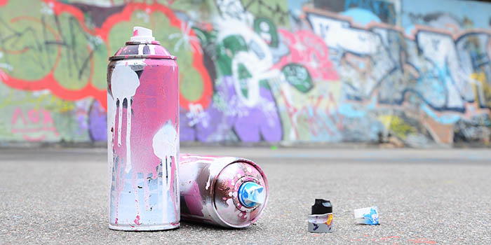 Several used spray cans with pink and white paint and caps